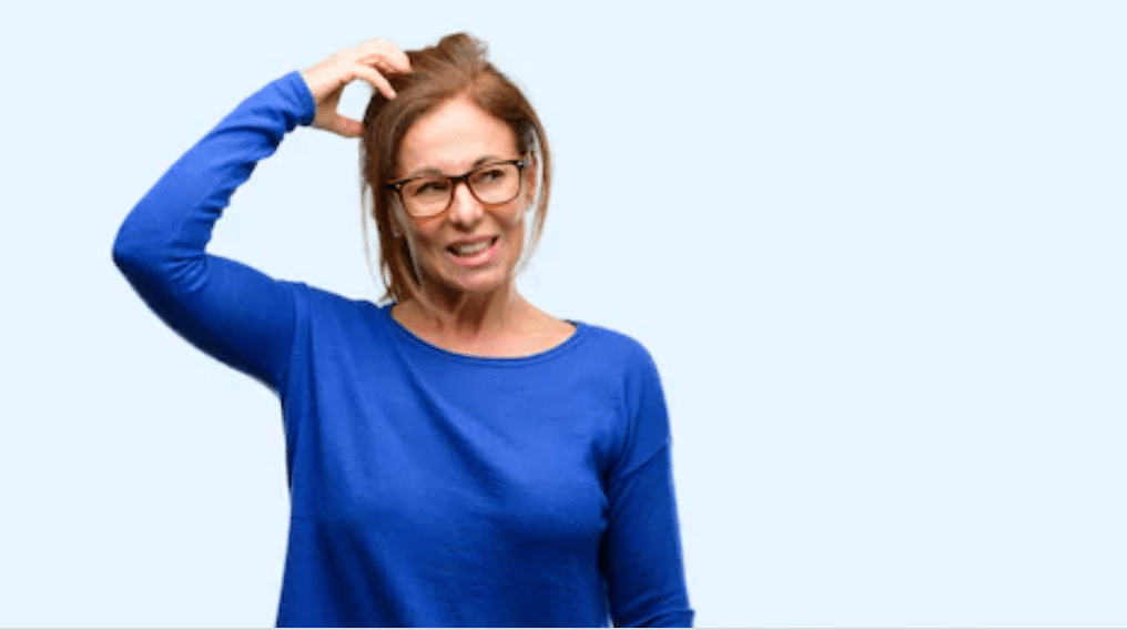 Woman scratching her head in a confused manner